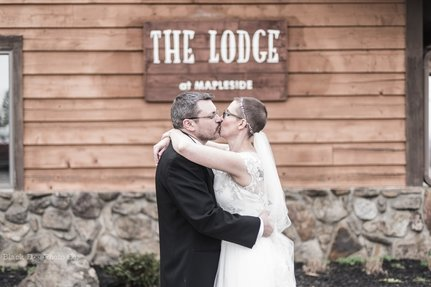 Wedding kiss in front of the Lodge at Mapleside Farms