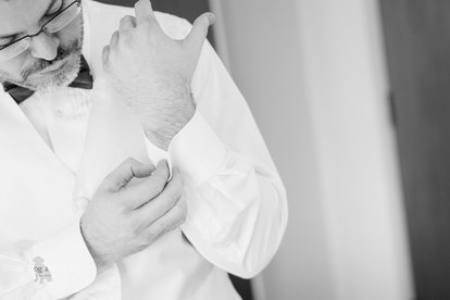 A wedding photo of a groom putting on his cuff links